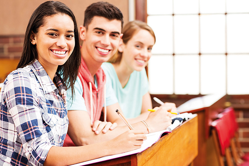 Female Student With Friends Sitting At Desk In Classroom